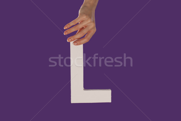 Female hand holding up the letter L from top Stock photo © stryjek