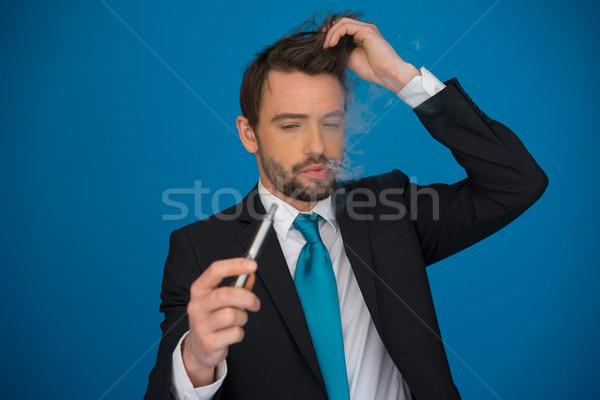 businessman with e-cigarette wearing suit and tie on blue Stock photo © stryjek