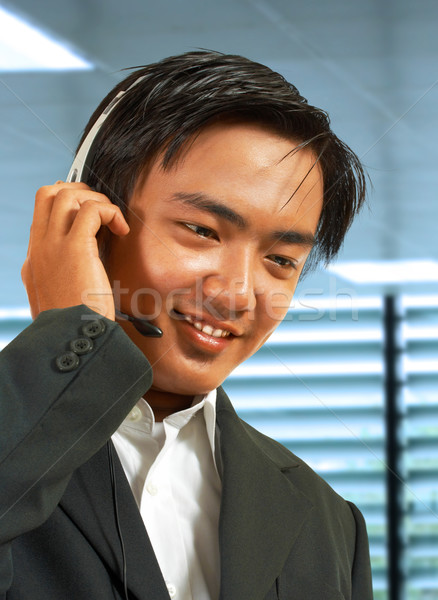Male Sales Representative In His Office Talking On A Headset Stock photo © stuartmiles