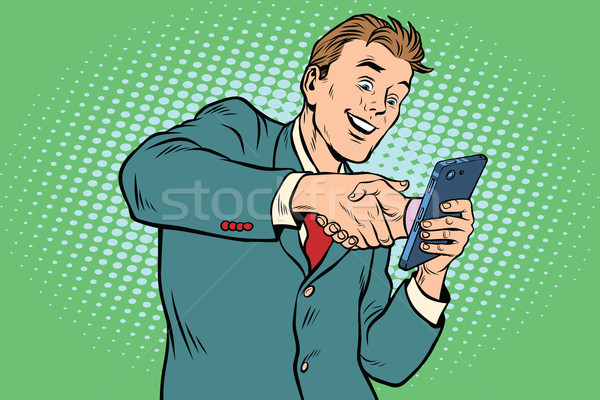 business handshake via smartphone Stock photo © studiostoks