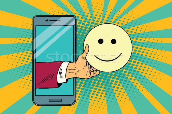 smile joy emoji emoticons in smartphone Stock photo © studiostoks