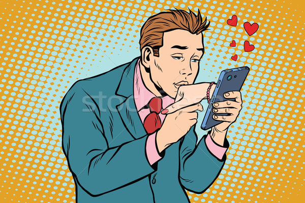 online date and love a man kisses a womans hand via smartphone Stock photo © studiostoks