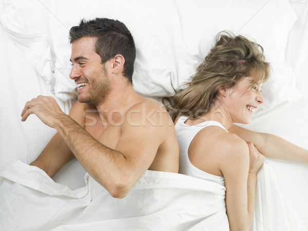 attractive couple in love laughing in bed Stock photo © Studiotrebuchet