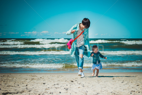 mother and daughter run on the beach stock photo
