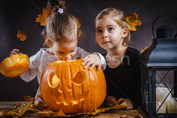 Two girls play with a Halloween pumpkin Stock photo © superelaks