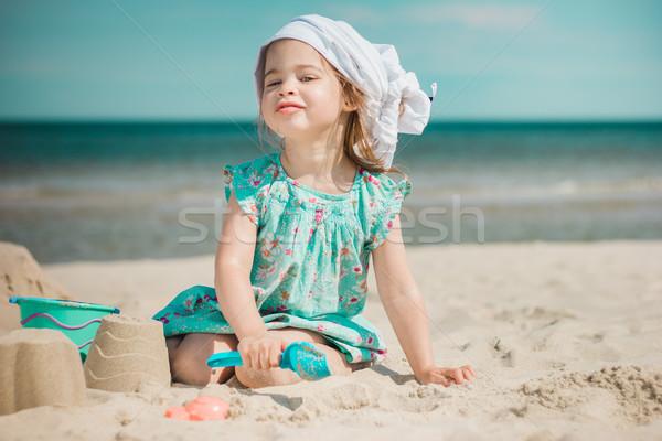 Fiatal lány készít homokvár tengerpart napos víz Stock fotó © superelaks