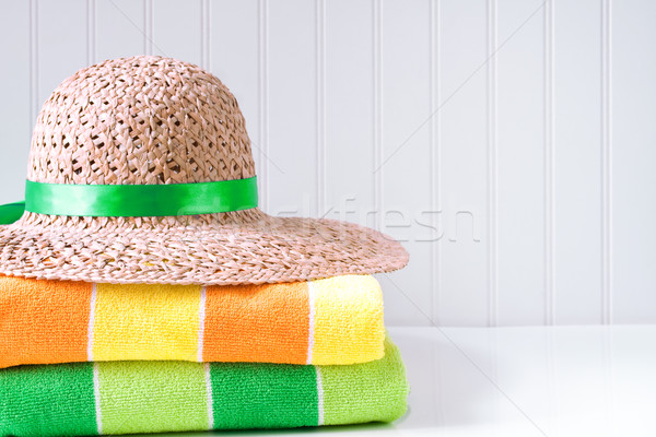 Straw hat with beach towels Stock photo © susabell