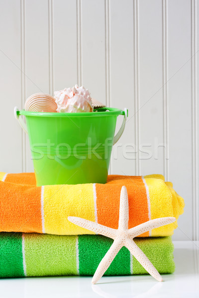Beach towels with starfish and sand bucket Stock photo © susabell