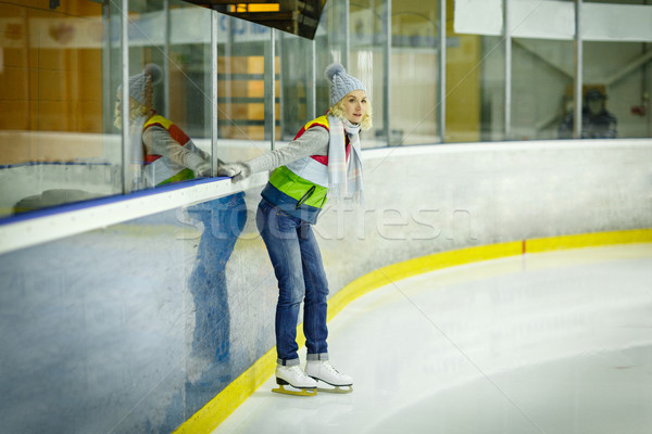 Beautiful girl in winter clothes and skates on ice rink Stock photo © svetography