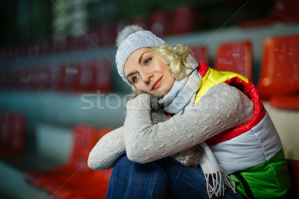 Beautiful girl in winter clothes sitting on rink tribune Stock photo © svetography