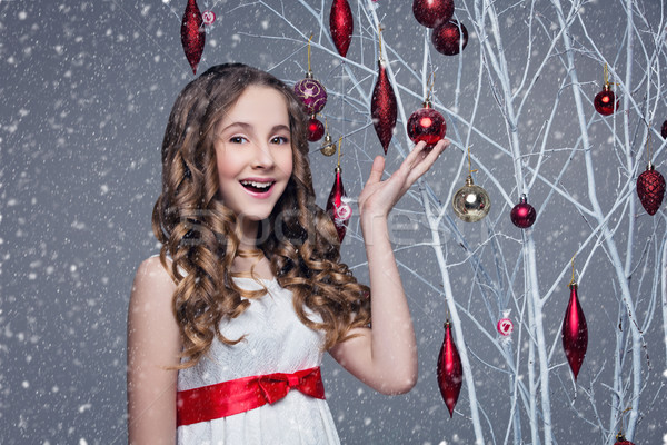 Beautiful girl standing near tree with christmas decorations Stock photo © svetography