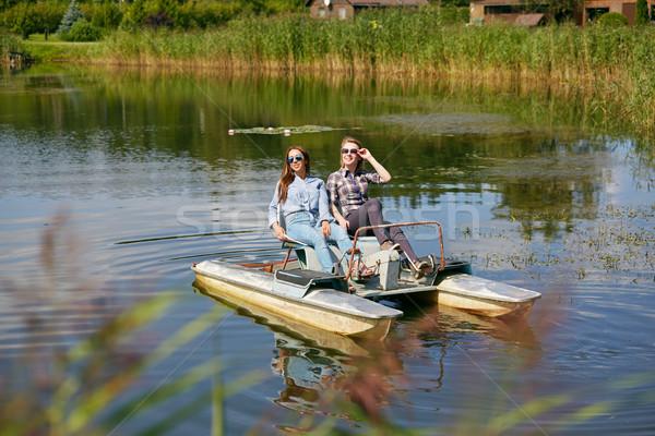 Dos ninas catamarán las mujeres jóvenes equitación lago Foto stock © svetography