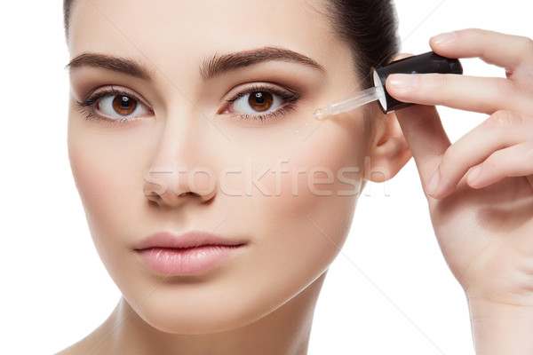 Girl applying eye serum Stock photo © svetography
