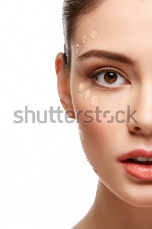 girl applying foundation on face isolated on white Stock photo © svetography