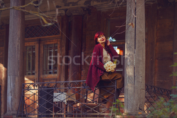 Girl sitting on old house balcony Stock photo © svetography