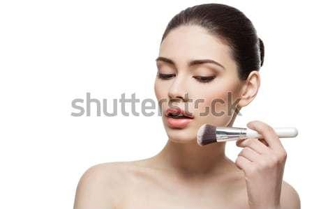 Beautiful girl applying powder with brush Stock photo © svetography