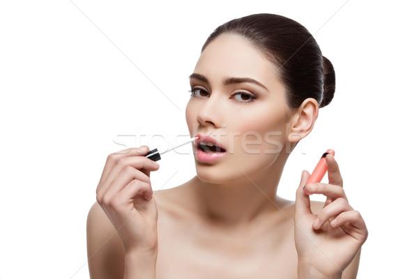 Beautiful girl applying lipgloss Stock photo © svetography