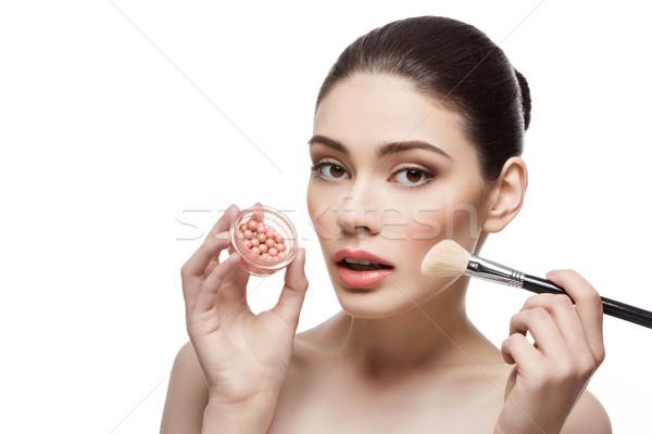 Beautiful girl applying blush with brush Stock photo © svetography