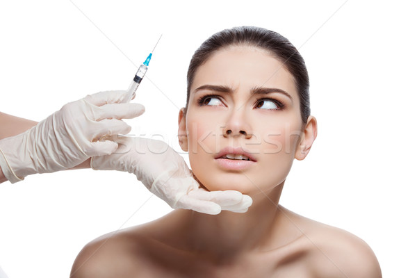 Scared girl looking at syringe Stock photo © svetography