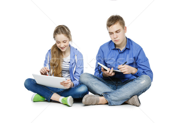 Teen age boy and girl with tablet and notebook Stock photo © svetography