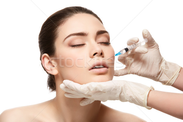girl getting face injection isolated on white Stock photo © svetography