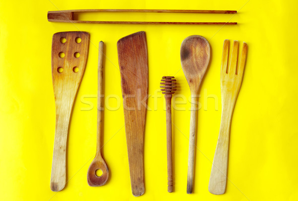 Old wooden spoons and stirrers on yellow background Stock photo © szabiphotography