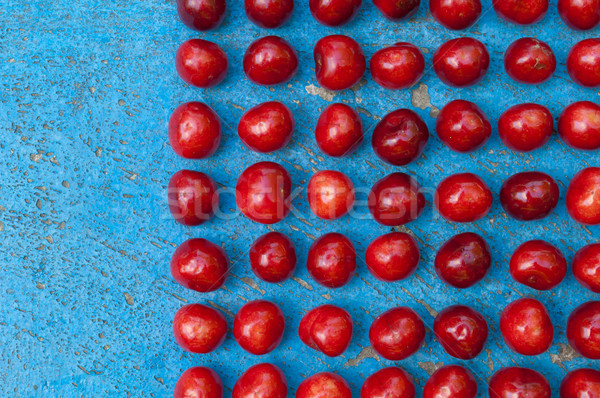 Arrangement of ripe cherries on blue textrured background Stock photo © szabiphotography