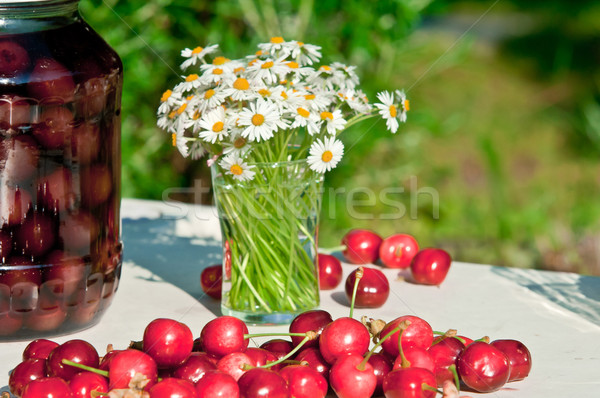 Fresh Cherry bottled cherry and daisy flowers on table in spring Stock photo © szabiphotography