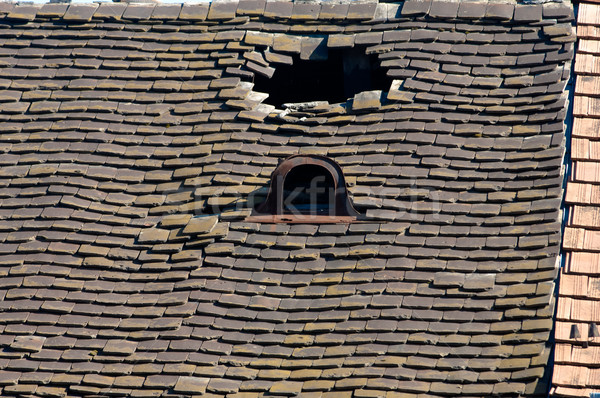 Old damaged tiled roof with a hole on the roof and broken tiles Stock photo © szabiphotography