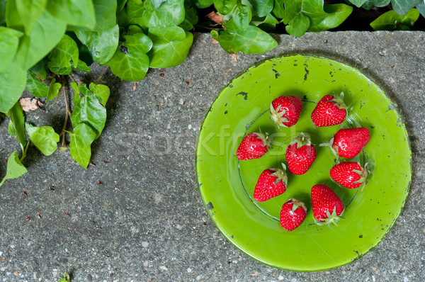 Delicious ripe strawberry  on green plate on grey stone flat lay Stock photo © szabiphotography