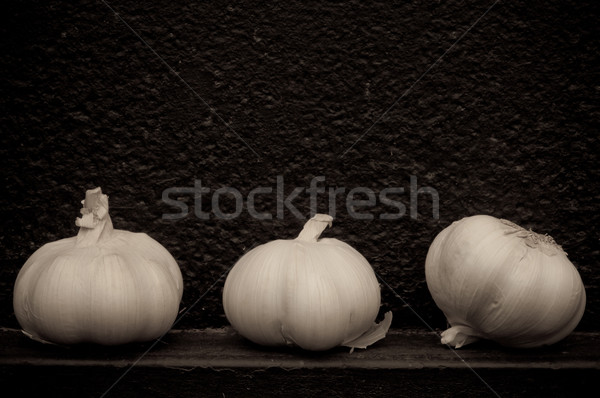 Garlic in front of rough textured black background Stock photo © szabiphotography