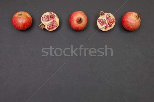 Whole and cut pomegranates in row on dark grey background Stock photo © szabiphotography