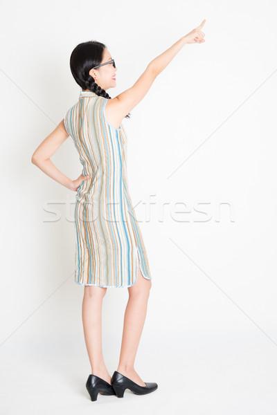 Asian girl pointing at something Stock photo © szefei