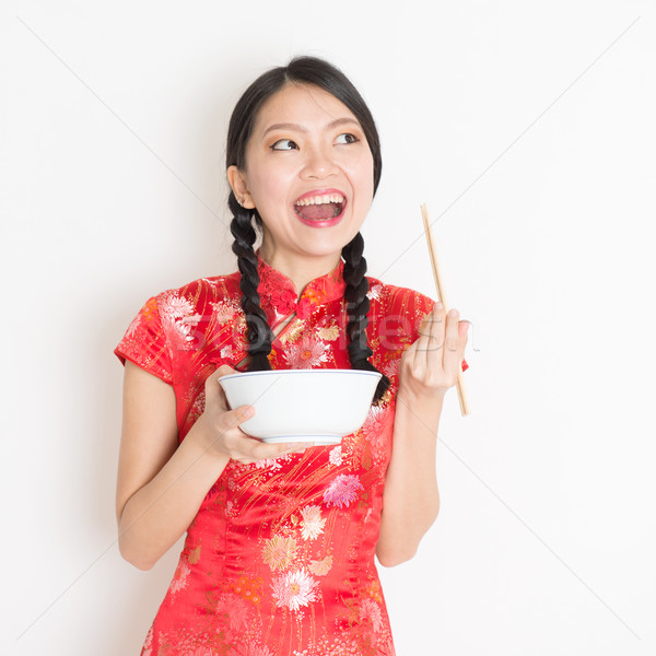 Oriental woman in red qipao eating with chopsticks Stock photo © szefei