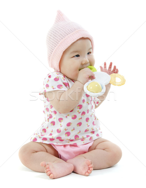 Asian baby girl biting on teething toy Stock photo © szefei