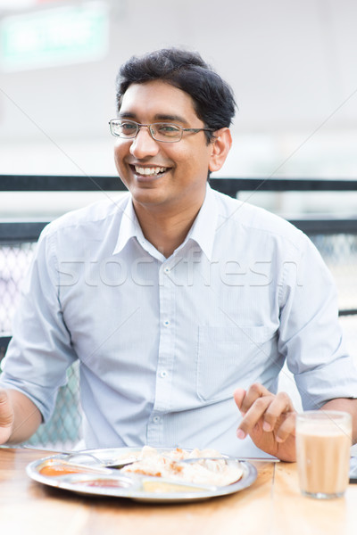 Happy man eating food at cafeteria. Stock photo © szefei