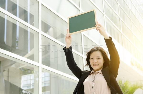 Young Asian business woman showing blank chalkboard Stock photo © szefei