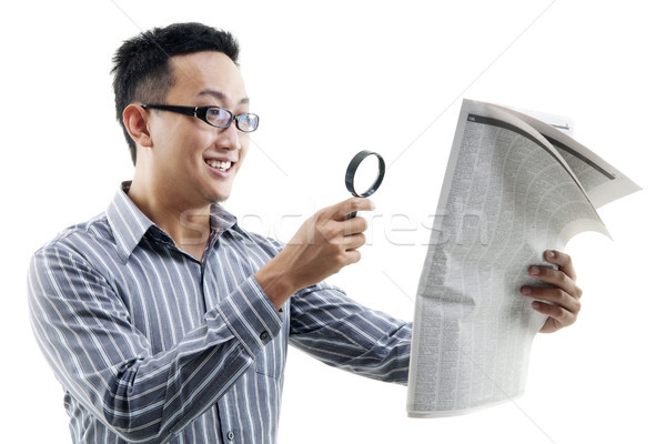 Asian man reading newspaper with magnifier Stock photo © szefei