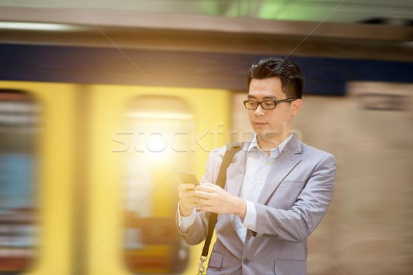 Stockfoto: Smartphone · treinstation · asian · zakenman · wachten