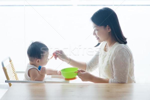 Mother feeding toddler. Stock photo © szefei