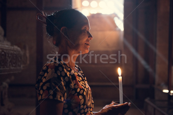 Old wrinkled traditional Asian burmese woman praying with candle light inside a temple, low light, M Stock photo © szefei