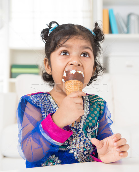 Stock photo: Indian girl eating ice cream.