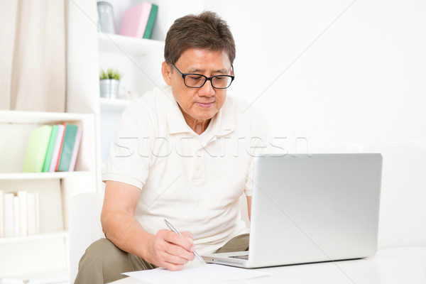 Mature Asian man using computer Stock photo © szefei