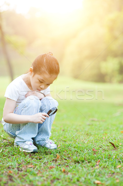 Kid exploring nature with magnifier glass at outdoors. Stock photo © szefei