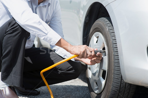 Filling air to the car tires. Stock photo © szefei