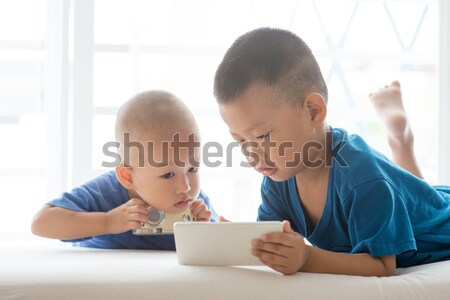 Young children addicted to smartphone. Stock photo © szefei