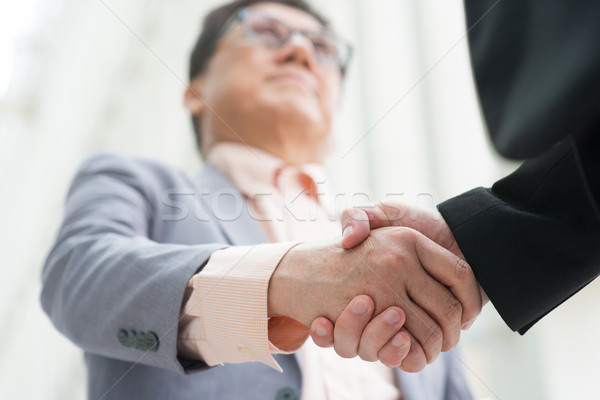 Asian business men handshaking Stock photo © szefei