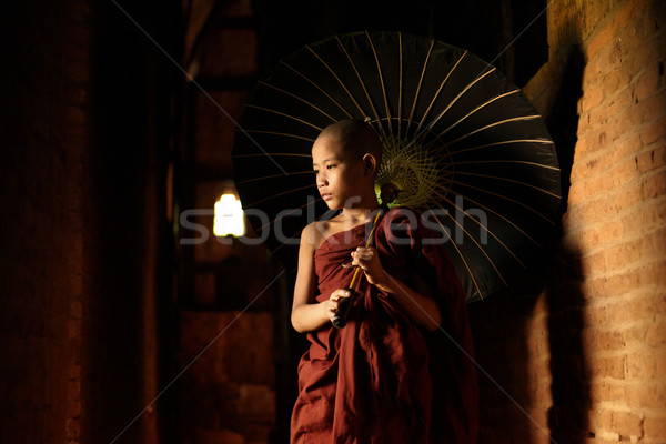 Buddhist novice walking with umbrella Stock photo © szefei