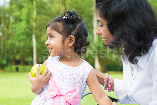 Indian girl holding an green apple outdoor Stock photo © szefei