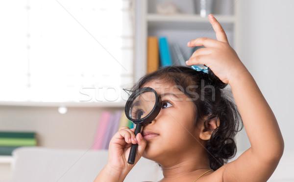 Indian girl peeking through magnifying glass. Stock photo © szefei